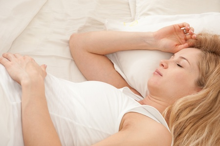 lying down: Young pregnant blonde woman sleeping in bed Stock Photo