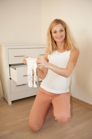 Young pregnant blonde demonstrates her babys tights photo
