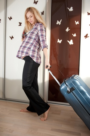 Young pregnant blonde with suitcase ready to travel photo