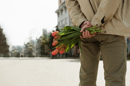 Young man is waiting for his girlfriend with tulips photo