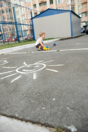 Little boy is playing with cars outdoors photo