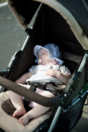 Little baby girl is sleeping in stroller photo