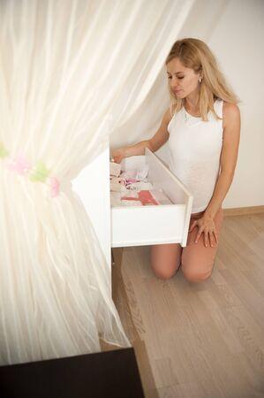 Junge schwangere blonde Frau sitzt an ihrem Baby Kleidung suchen