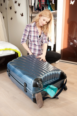 Young blonde pregnant woman packing travel bag at home photo