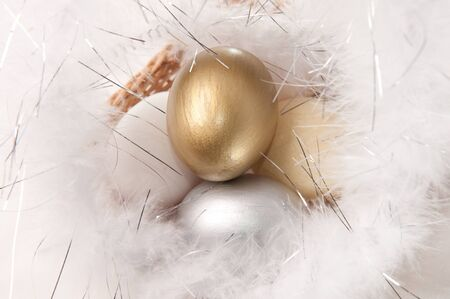 Easter eggs on fur background. Golden, silver, white and yellow colors. photo