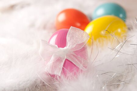 Colorfull vibrant Easter eggs on feather background photo