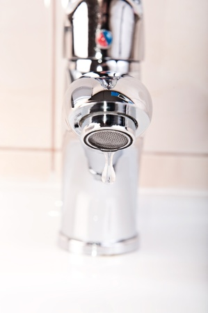 Modern faucet closeup with cute water drop photo