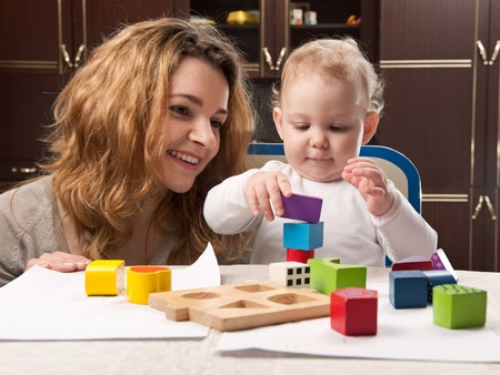 children playing with toys: Young mother and her little baby daughter building tower with toy blocks