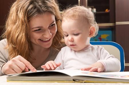 niños leyendo: Joven madre y su pequeño libro de lectura hija Foto de archivo