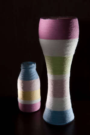 Two yarn wrapped colorful striped glass bottles photo