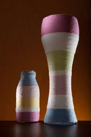 Two yarn wrapped colorful striped glass bottles Stock Photo - 12549929