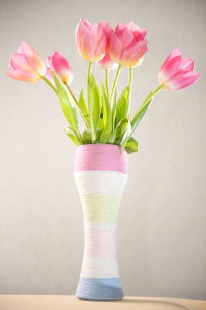 tulips in vase: Custom yarn wrapped vase with pink tulips Stock Photo