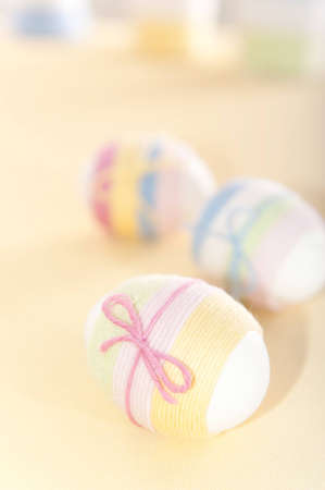 Custom handmade yarn wrapped Easter eggs over yellow background photo