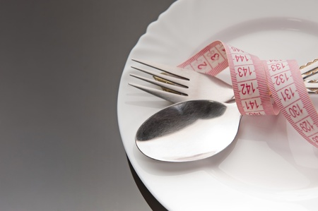 Empty plate with a spoon, fork and measuring tape photo