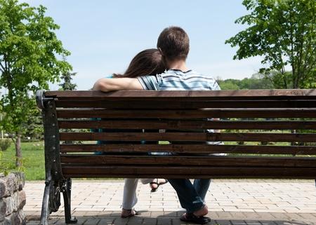banc de parc: Jeune couple assis sur le banc en vue au stationnement arrière Banque d'images