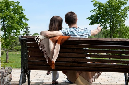 Young couple sitting on bench in park  Rear view