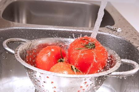 colander: Three fresh tomatoes in colander splashing in water Stock Photo