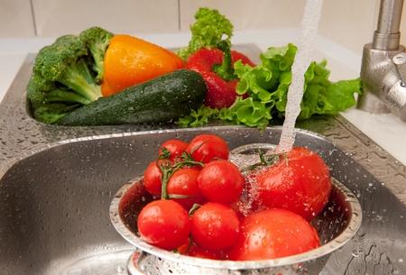 Verdura fresca spruzzi in acqua prima della cottura
