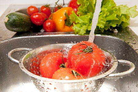 Three fresh tomatoes in colander splashing in water photo