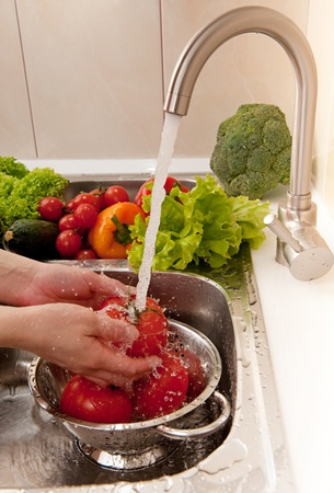 a colander: Washing tomatoes under water in colander Stock Photo