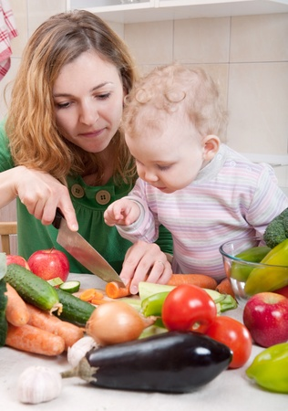 Young mother preparing fresh vegetable salad with her baby daughter photo