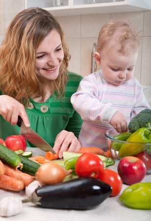 Young mother preparing fresh vegetable salad with her baby daughter Stock Photo - 13071042