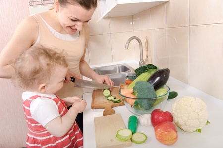 Young mother preparing fresh vegetable salad with her baby daughter Stock Photo - 13070878