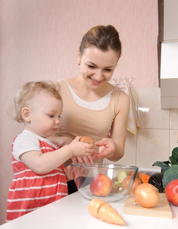 Young mother preparing fresh vegetable salad with her baby daughter Stock Photo - 13070729