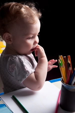 Little baby girl drawing with colorful pencils photo
