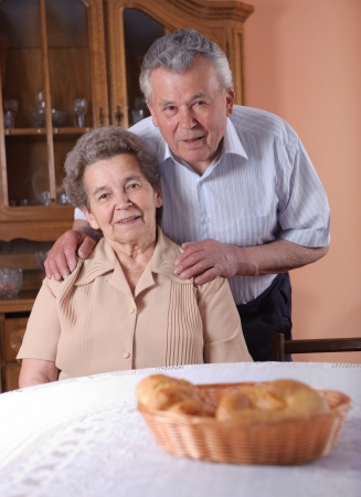 Happy senior couple at the table indoors. Hands on shoulders. Stock Photo - 13822996