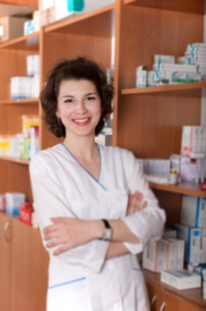 Young female chemist in uniform in drugstore photo
