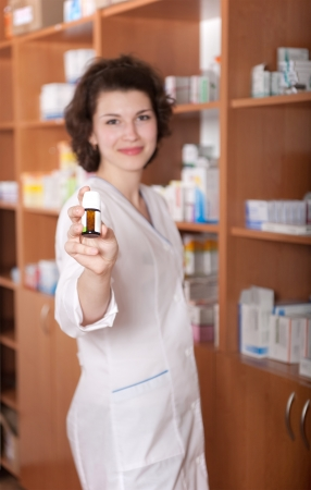 Young chemist in drugstore showing bottle of pills. Primary focus on bottle. photo