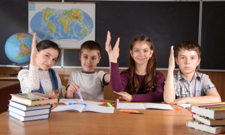 Four schoolchildren aged 11 at the desk in classroom photo
