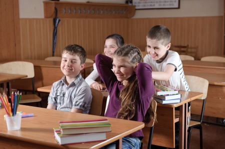 pulling hair: Pupils aged 11 sitting at the desks in classroom Stock Photo