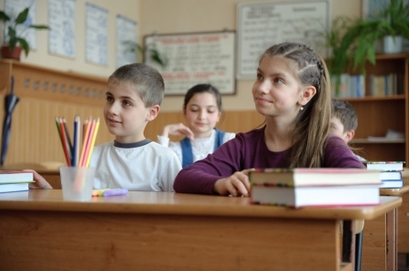 11: Pupils aged 11 sitting at the desks in classroom Stock Photo