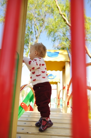 Cute baby girl standing on playgrounf over trees background Stock Photo - 13873132