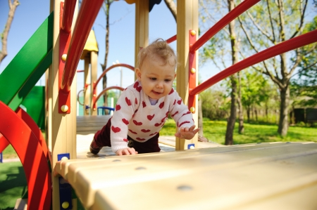 Excited little baby girl crawling on playground Stock Photo - 13873109