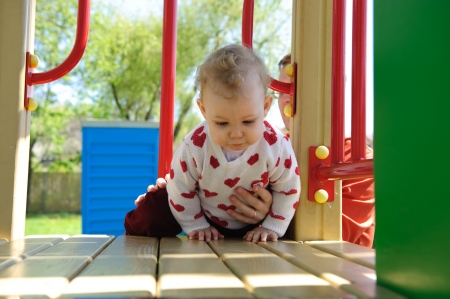 Excited little baby girl crawling on playground Stock Photo - 13873107