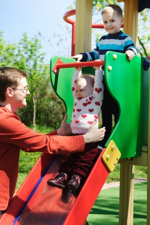 Young father halping his children to slide on playground photo