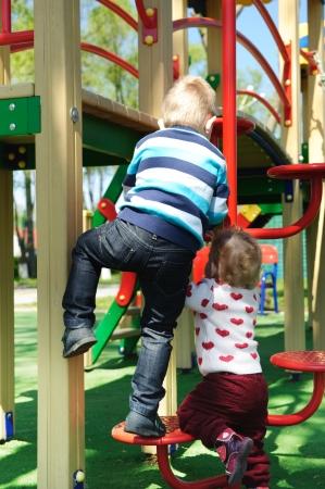 niño escalando: Hermano y hermana en el patio de la escalada