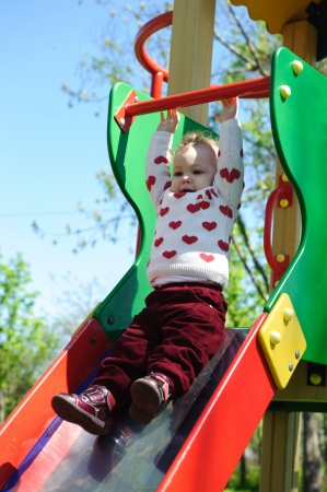 Cute little girl is hanging on a slide on playground Stock Photo - 13873108