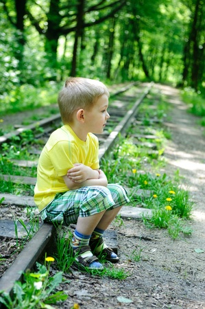 homeless children: Little boy is sitting on railroad rails