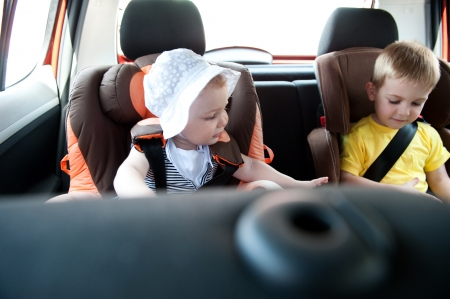 Little brother and his baby sister travelling in baby car seats Stock Photo - 13873130