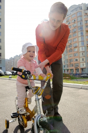Young father assists his little daughter riding a bicycle photo