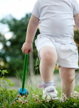 step daughter: Cute child is walking in green grass Stock Photo