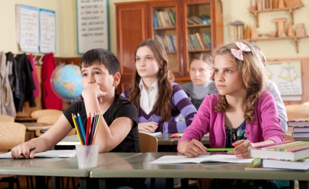 bored student: Group of schoolchildren at classroom during a lesson Stock Photo