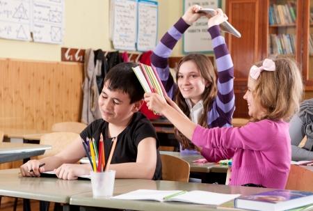 niños malos: Scholchildren adolescentes luchando con los libros en el aula en la escuela