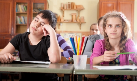 Bored boy sleeping and dreaming during a lesson in classroom Stock Photo - 14469151