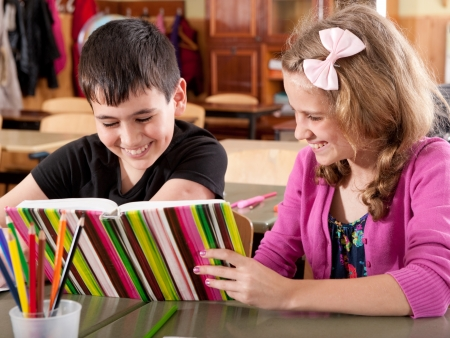 Happy smiling boy and girl reading book at school during a lesson photo