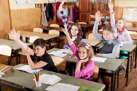 Group of schoolchildren at classroom during a lesson raising hands photo